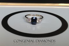 Elegant three stone ring set with a sapphire and two round brilliant diamonds