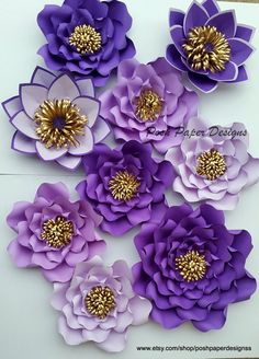 Shades of purple and gold paper flowers 1 large 8 medium Can be made in any size or color Each flower is individually designed and custom made. Each flower may slightly vary in design since it is custom made. Our Paper flowers can also be customized with business logos, names, dates etc. ------Installation------- Our paper flowers come with wire/ribbon hangers for easy installation. You can hang flowers using thumb tacks, command strips or safety pins on fabric. -------Shipping------ Ple...