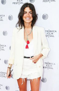 Leandra Medine of the Man Repeller wears a white v-neck tank top, white cutoff shorts, a skinny black belt, creme blazer, and finishes it off with a colorful tassel necklace