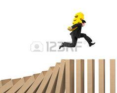 Hombre que lleva el signo del Euro, corriendo antes que se caigan las fichas del dominó de madera.