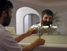 Yitzy Kasowitz places a LEGO Menorahs on the fireplace mantel at his Highland Park home in St. Paul on Wednesday, Dec.