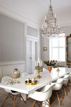 Beautiful white dining room complete with chandelier.