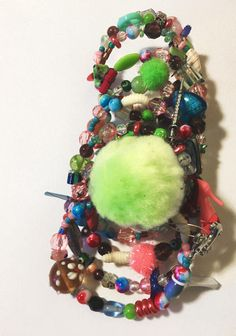 The bracelet youve all been waiting for! The reek of cologne and powder and rotting flesh. Maggots slither across an open jewelry box. A dark story hides in this bracelets colorful appearance. Millefiori beads, pom poms, plastic beads, an aged lipstick charm, glass beads, and yes,
