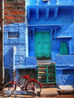 India, Jodphur, the blue city, brightly blue coloured building, red bicycle