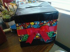 comic book theme wedding. Handmade, Made from cardboard box, black spray paint (glossy finish), and fabric and red ribbon from Walmart