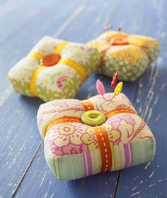 Bold fabrics, bright buttons, and colorful ribbon elevate practical pincushions to new heights.