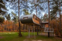 Architecture. Modern-contemporary Tree House Come With Silver Metal Roof And Flooring With Curved Over Hang And Landscape Small Window And Earth Yellow Wood Wall With Rectangular Clear Glass Window Include Silver Iron Long Straight Legs As Column Furthermore Silver Iron Half Landing Stairs As Well As .