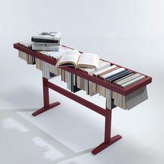Prateleira de leitura engenhosa se transforma em uma mesa para livros. Foi projetada para abrigar os livros nas páginas marcadas enquanto as costas dos livros criam uma superfície lisa servindo de mesa.