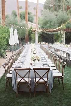 A long, romantic reception table with floral centerpieces, crisp-white dinnerware, and rustic cross-back chairs.