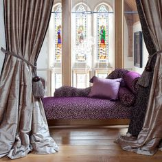 Purple chaise and beautiful silk drapes.