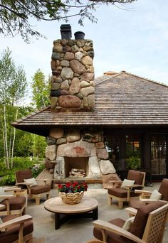 pebble rock outdoor fireplace with backyard chairs around a firepit