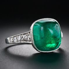 A gorgeous glowing green gumdrop, weighing 5.00 carats, speaks mostly for itself in this elegantly restrained platinum and diamond Art Deco mounting - circa 1930. This fabulous old mine cabochon emerald resides in a delicately milgrained bezel