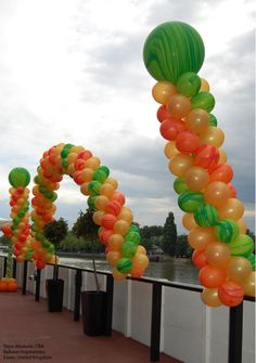 This eye-catching Arch and coordinating Columns combine unique Qualatex Rainbow SuperAgate latex balloons with Gold latex for a striking color combo. Design by Tope Abulude, CBA, of Balloon Inspirations in Essex, United Kingdom.  Find a balloon professional near you: http://www.qualatex.com/balloons/findapro.php