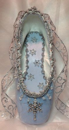 "Lovely Snow-Themed Pointe Shoe. Pale blue & covered w/ a sheer organza fabric printed w/ sparkly silver swirls. There's a beautiful rhinestone snowflake w/ a dangling crystal as the focal point & there are numerous other snowflakes scattered on the inner sole. The trim has clear ""icicles"" dangling along the edge. The outer sole's painted white 