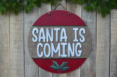 SANTA IS COMING big christmas wooden ornament. An entirely handmade wooden christmas sign is here to complete your Christmas decoration. You can hange it in your living room or your door you can give it as a gift to a friend or a family member.  If you want this year to decorate your home with something unique, thats your chance. This handmade wooden sign is an OOAK product that you wont find anywhere else. ❂ P R O D U C T I O N P R O C E S S ❂  The thing that makes these wooden signs really…