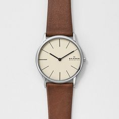 "Skagen Men's SKW6083 ""Theodor"" Stainless Steel Watch with Brown Leather Band. Round watch in stainless steel with beige dial, slender stick hour markers, and logo at 3 o'clock. Quartz movement with analog display. Protective mineral crystal dial window. Features calfskin leather band and buckle closure. Water-resistant to 99 feet (30 M): withstands rain and splashes of water, but not showering or submersion."