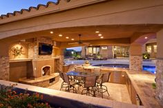 viking outdoor kitchen stone fireplace marble countertop pool chairs dining table stove cabinets island drawers ceiling lights fan traditional style of Stunningly Cool Viking Outdoor Kitchen Designs to be Inspired By