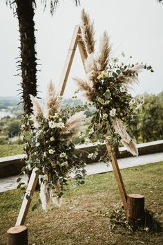 Wooden Arch with Foliage and Pampas Grass Decor   By Benni Carol Photography   Italian Wedding   Italy Wedding   Pampas Grass Decor for Wedding   Outdoor Wedding   Boho Wedding   Long Sleeve Wedding Dress   Flower Crown for Bride   Wedding Dresses With Flowers, White Wedding Dresses, Boho Wedding Dress, Flower Dresses, Wooden Arch, Boho Wedding Decorations, Applique Wedding Dress, Pampas Grass, Italy Wedding