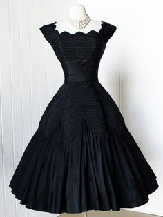 1950's black silk fortuny cocktail party dress in the classic silhouette, with an amazing fortuny pleated, fitted bodice and petal panels around the skirt,  fabulous neckline, boning around the waist for structure, and a full circle skirt. by Ceil Chapman.
