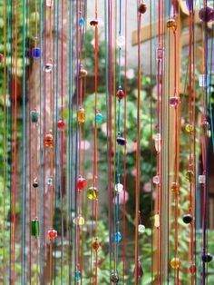 Entre deux averses j'ai bricolé un rideau de porte ( contre les mouches, je déteste les mouches autour de mon lustre !) Sur un rideau de fils à 5 euros j'ai enfilé des perles de verre de couleurs qui prennent bien la lumière ... Voilà qui j'espère dissuadera...