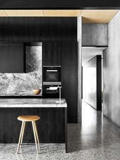 Modern kitchen with black cabinents, a marble backsplash, and a wooden stool