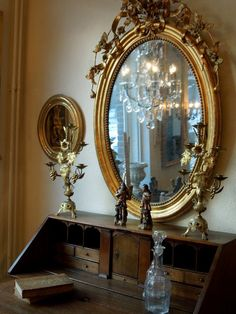 this ornate mirror reflects the chandelier, giving the room extra sparkle!
