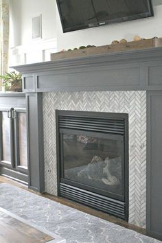 Tiling a fireplace surround. Love the herringbone tile and gray fireplace surround. from ThriftyDecorChick Fireplace Tile Surround, Grey Fireplace, Fireplace Update, Home Fireplace, Fireplace Remodel, Fireplace Surrounds, Fireplace Design, Fireplace Makeovers, Fireplace Ideas