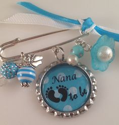 """This beautifully made blue and white """"Nana To Be"""" brooch is perfect for a soon to be Nana. A wonderful gift to give your precious loved one at a baby shower. I've embellished this brooch with color coordinated ribbon, color coordinated beads, baby feet charm and a one inch bottle cap pendant attached to a looped safety pin. This brooch can be completely customized from ribbon, beads to the design of the pendant. example...Mom to Be, Granny to Be, or any words of your choice."""