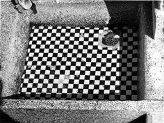 Gootsteen met afvoerputje. Zwart-witte tegeltjes, in een granieten aanrecht. Typerend voor de jaren vijftig-keuken.