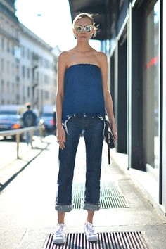 We spotted this denim-on-denim street style look that's great for beating the heat in style this summer. The ultra-cool look consists of mirrored sunglasses, a strapless top, raw hem boyfriend jeans and white sneakers.
