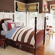 Boys bedroom with striped duvet, wainscoting, chocolate brown paint, four post bed, roman shades