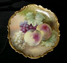 "This is a beautiful antique Limoges porcelain still life charger/plaque with fruit and foliage.    It is an exquisite piece signed on the front by one of the most sought after Limoges factory approved artist's ""Dubois"".       The original mold has scalloped edges and detail work near the edge. These areas are heavily gilded and the gilding is 99% intact!   It is marked with the Flambeau Limoges Mark 5. This dates this piece 1891 to 1914."