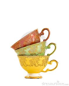 Stack of three brightly coloured vintage china teacups in yellow, green and red with pretty gold design. Isolated on white background.
