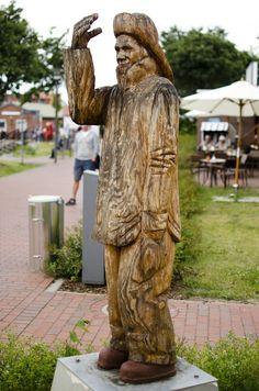 #Heiligenhafen Aus einem Baumstamm geschnitzt, grüßt ein junger Fischer die Passanten, die linke Hand lässig in der Hosentasche und wetterfest gekleidet. Junger Fischer aus Holz. 23774 Heiligenhafen.