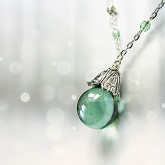 Mint glass orb and silver bell fantasy necklace pendant by JantraK: made with an upcycled oily glass marble and delicate silver tone chain adorned with sparkling glass crystal beads