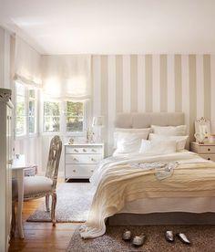 Habitación juvenil con cama con cabecero capitoné, mesilla de noche, tocador con silla clásica decapada, pared de cabecero con papel pintado a rayas y alfombras