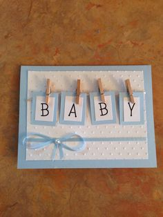"handmade baby shower card ... tiny clothespins attach boxes with ""baby"" spelled out ... blue and white could be changed to yellow, pink of any other color ... great card!!"
