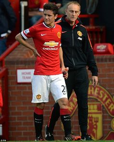 Herrera holds his rib as he leaves the Old Trafford pitch following his injury...
