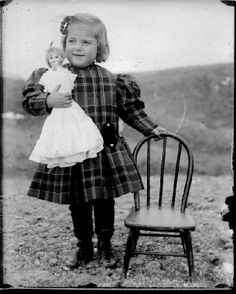 Sweet little girl with her doll and her chair.