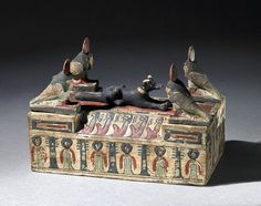 Painted wooden model box with four posts on which are four Ba-birds, in the centre is a dog. Ptolemaic Period. | The British Museum