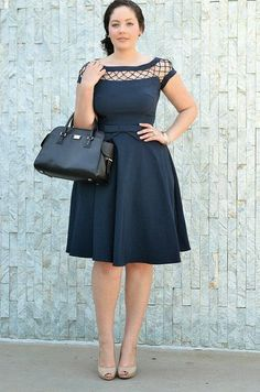 Dark navy blue cute stylish mini dress with black leather hand bag and cute high heels sandals