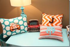 orange and aqua chevron, polkadots and striped pillows in a nursery.