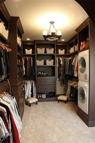 Clean clothes go straight from the dryer to the drawer in this walk-in closet, no hamper required. For efficiency, the homeowner opted for stacked machines and a built-in dresser that also serves as a folding table.