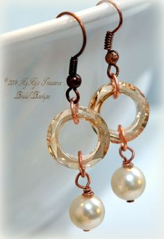These exquisite earrings feature Swarovski pearls dangling from sparkling Swarovski crystal cosmic rings in light topaz. The rings are linked to antique copper earwires. Choose from white, cream or creamrose pearls. Simple and elegant, these earring make a perfect accessory for brides, proms or any special occasion. $24.00  www.kykystreasuresbridalboutique.com