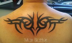 Symmetrical tribal tat This type of symmetrical tribal tattoo inked on the back is becoming more and more popular for men and women alike. Black upper back