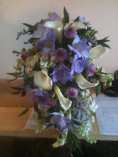 Lovely lavender freesias, with button mums and white mini callas on a bed of Italian ruscus for this trailing bouquet.