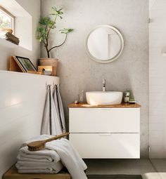 Basement bathroom.  White.  Concrete.  Wood.  Tropicals.  Continuous floor into the bathroom.  Shower tile ends with shower glass.  Feels bright and warm.  Woods are the highlights.