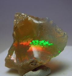 A rough piece of Opal that has a light yellow transparency.  I thought the fire was quite interesting, there are bands of dots in red and gr...