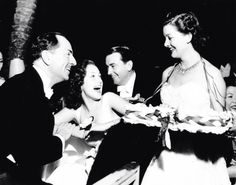 William Powell, his new wife Diana Lewis, Richard Barthelmess, and Myrna Loy acting as a cigarette girl at a Franco-British war relief party at the Cocoanut Grove, 1940