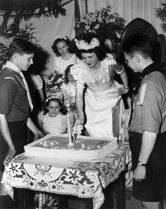 The May Queen slices into a large cake a a May Day festival, Vancouver, 1945. #vintage #Canada #1940s #holidays